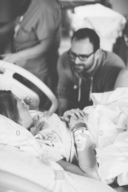 Man talks to his partner as she labors in delivery room