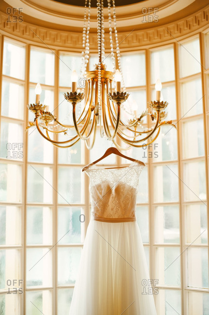 Wedding gown hanging from chandelier before rounded windows