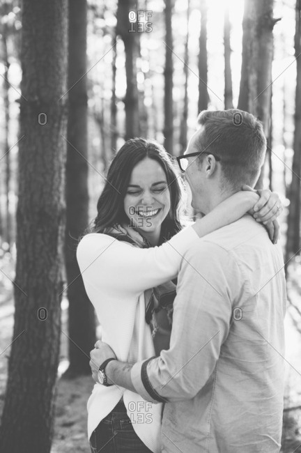 Young couple embraces in laughter in woods