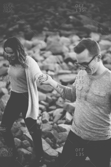Couple walking hand-in-hand over rocky terrain