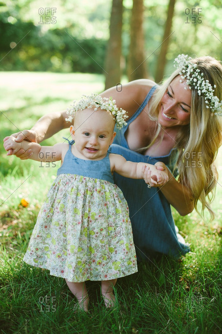 Mother and infant daughter wearing flower crowns outdoors