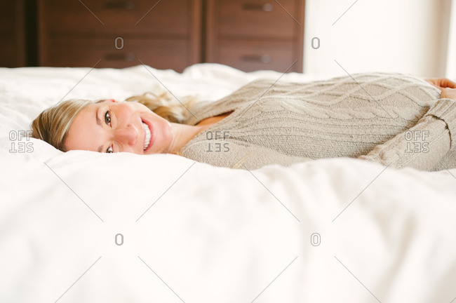 Portrait of expectant mother lying on bed