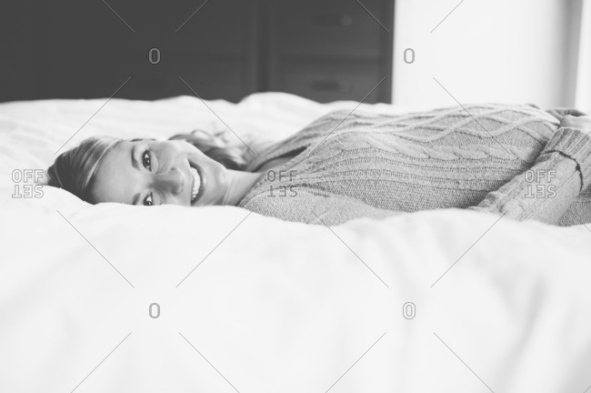 Happy expectant mother lying on bed