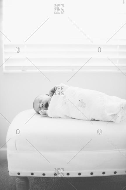 Swaddled newborn baby yawns on an ottoman