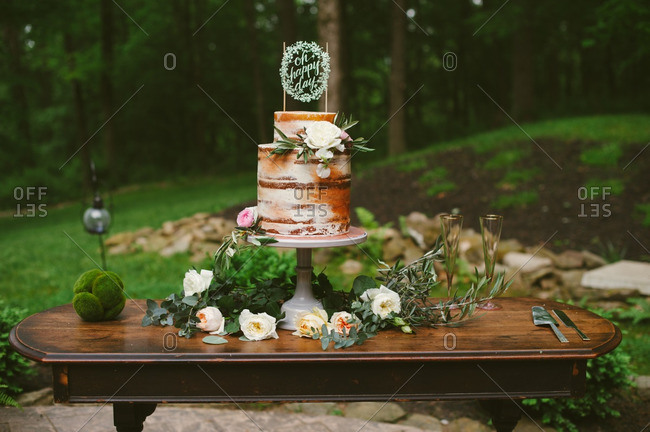 Rustic birchbark-decorated wedding cake on table outdoors