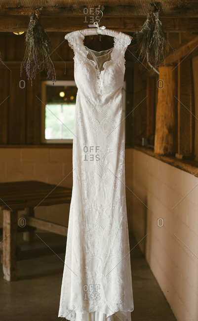 Wedding dress hanging from the rafters of barn