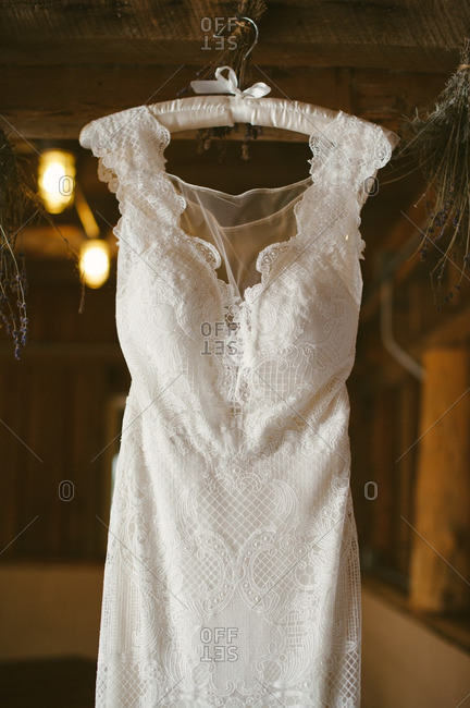 Close-up of a lace wedding dress hanging from barn rafters