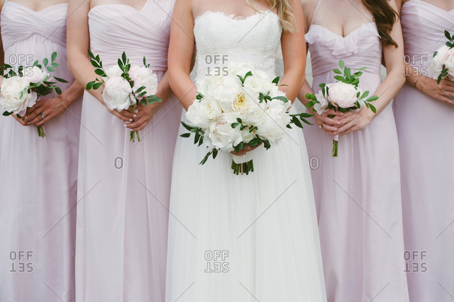 Neck-down portrait of bride and bridesmaids holding peony bouquets