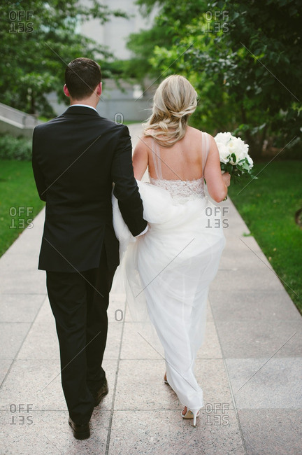 Groom holding back of bride's dress as they walk together on sidewalk