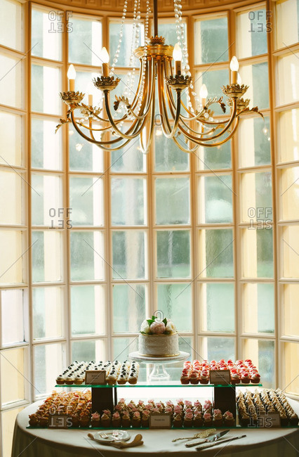 Dessert table by window under chandelier