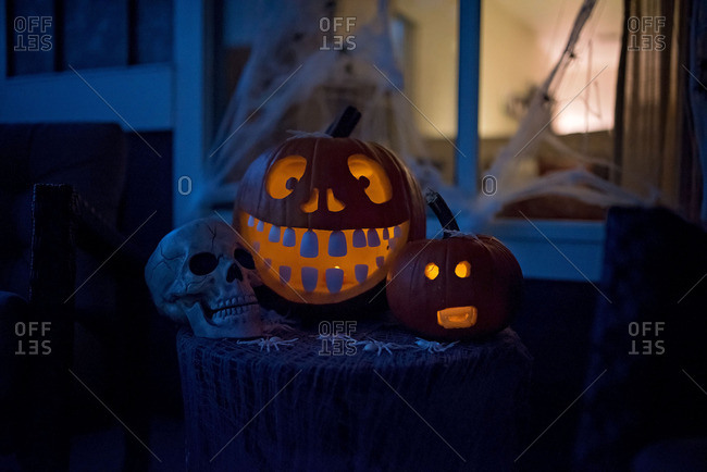 Jack-o-lanterns and skull arranged in a decorative display for Halloween