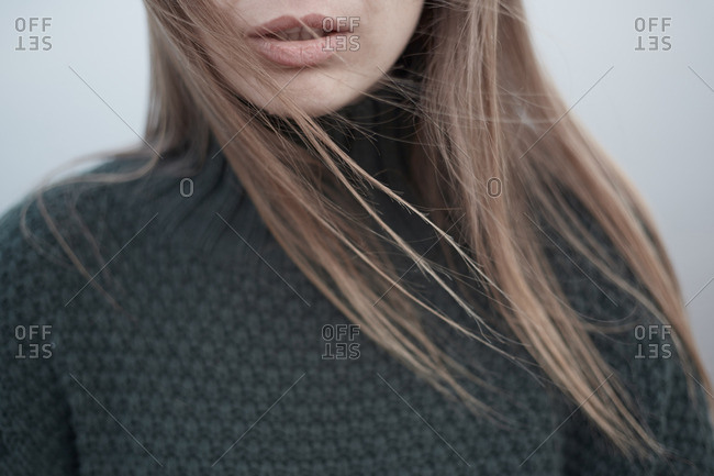 Close-up portrait of woman with long, blowing hair in gray sweater