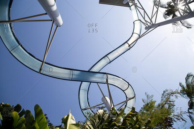 Upward view of transparent waterslide against blue sky