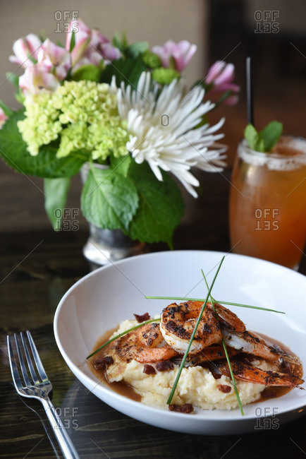 Bow of grilled shrimp served over grits with fresh chive garnish