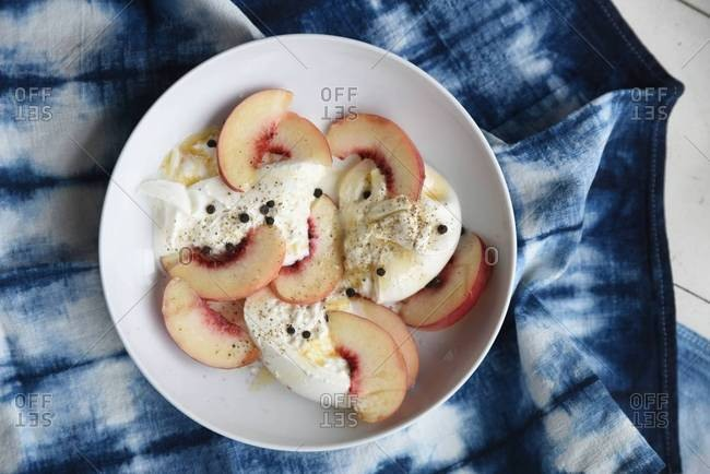 Plate of burrata and peaches with honey and black pepper