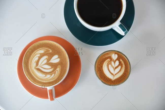 Overhead view of coffee drinks with heart designs in foam