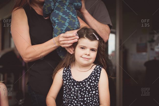 Multitasking mom holding baby and fixing daughter's hair