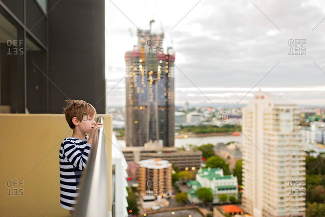 Boy peeking at city from balcony of high-rise