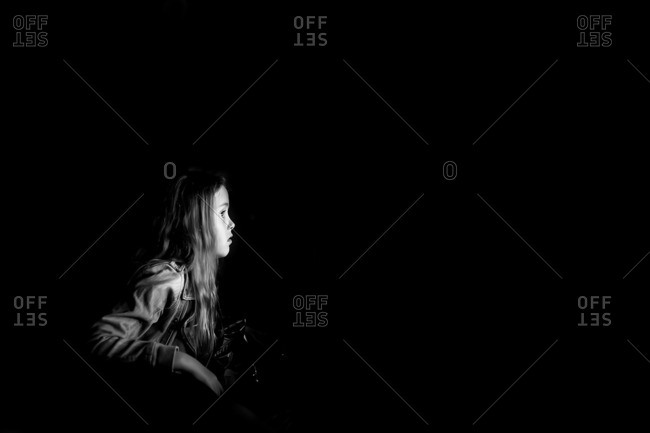 Girl illuminated by light of movie screen