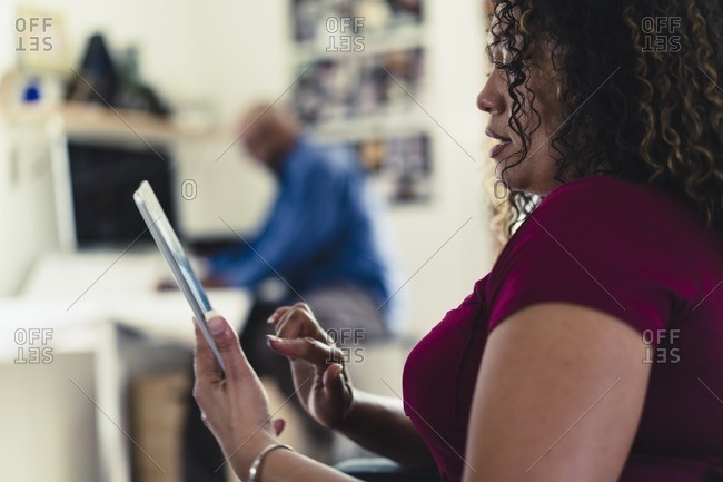 Woman using tablet computer with man at desk in background