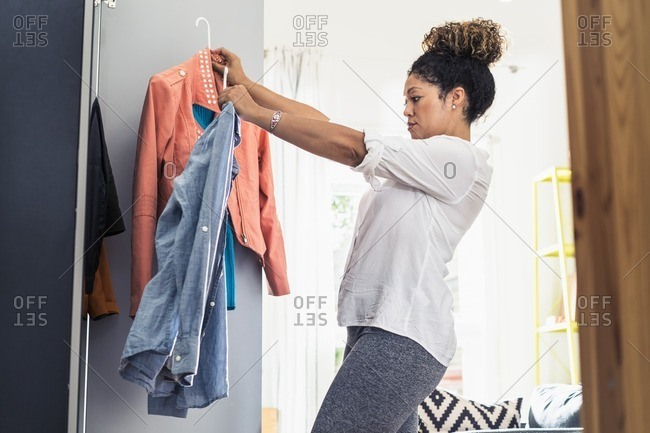 Woman deciding on outfit at closet
