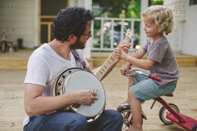 Father strumming a banjo as his son sits on a tricycle