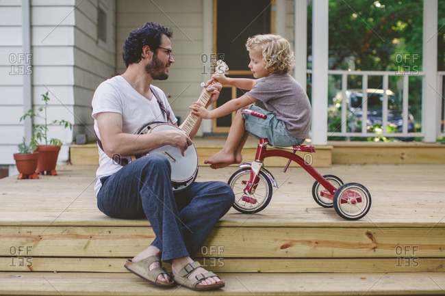 Man strumming a banjo as his son sits on a tricycle
