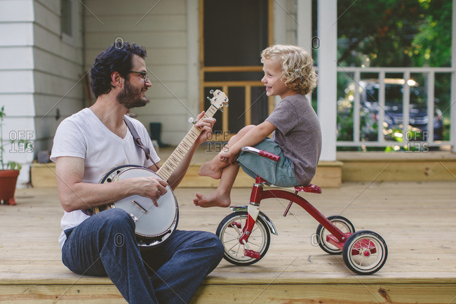 Boy sitting on his tricycle as his father strums a banjo