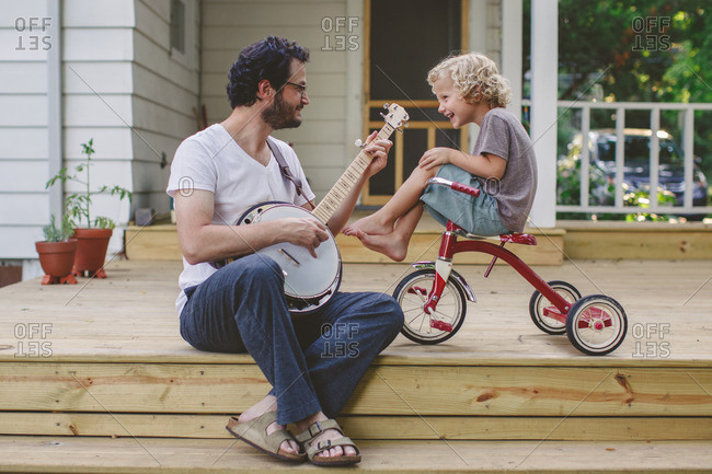 Boy sitting on a tricycle watching his father play a banjo