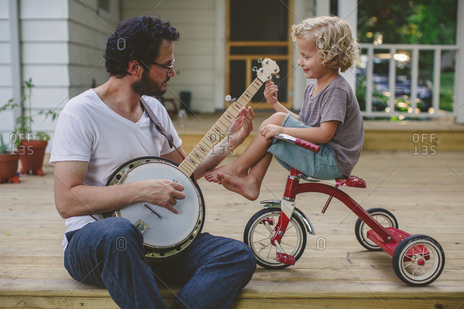 Man playing a banjo while his son sits on a tricycle and watches