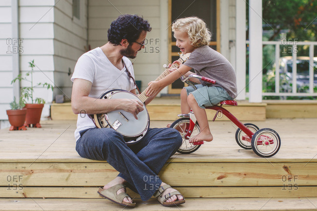 Man playing a banjo while his son sits on a tricycle