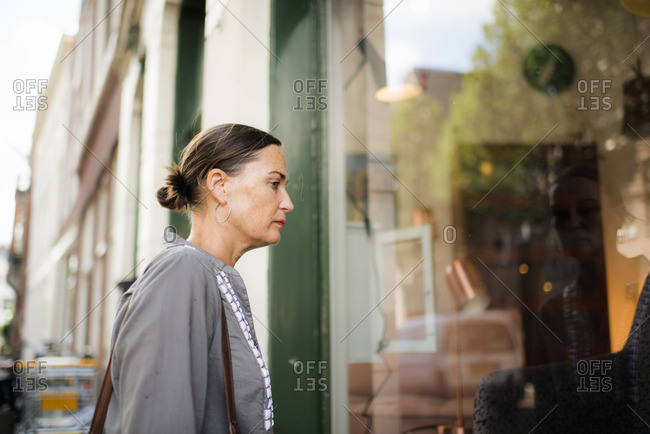 Woman on street looking into storefront