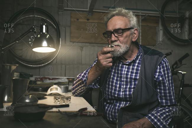 Man behind table in workshop lighting cigarette