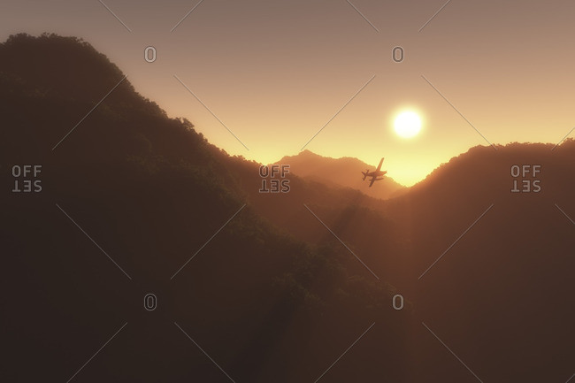 Sunrise over mountains with plane in sunbeam