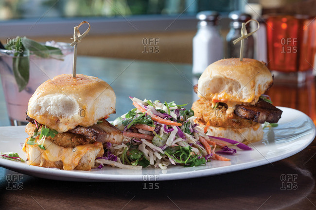 BLT sliders comprised of grilled pork belly, micro greens, fried green tomatoes, and house made pimiento cheese and slaw