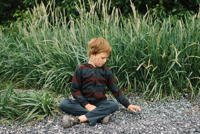 Boy sitting on ground playing with stones