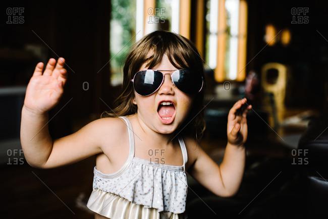 Little girl wearing aviator sunglasses and dancing