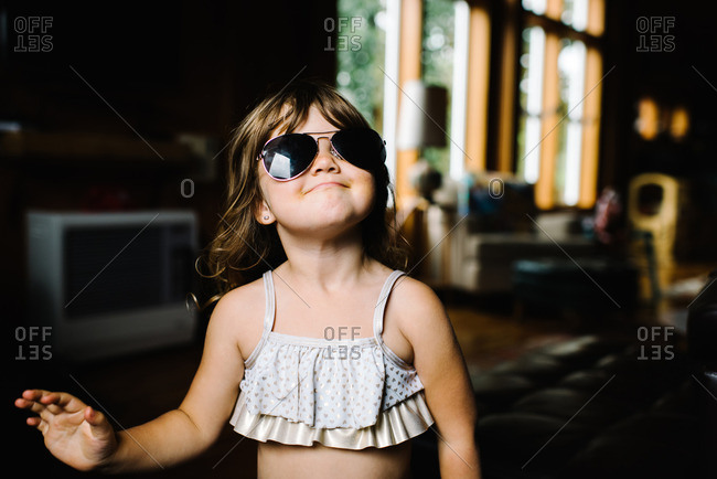 Little girl wearing swimsuit and aviator sunglasses
