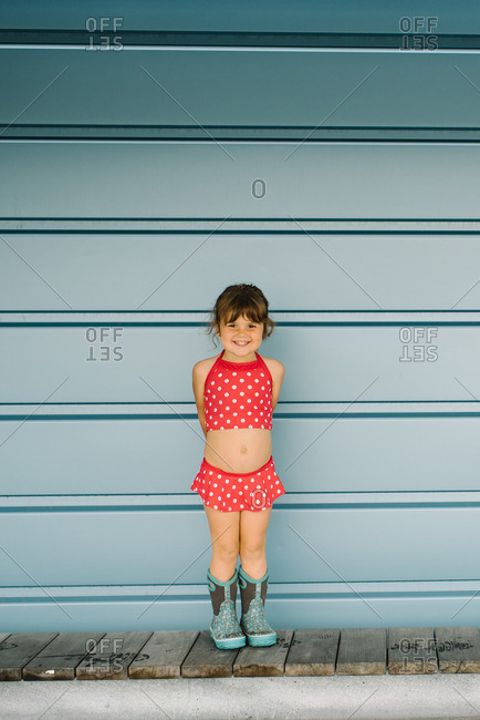 aa611923bd8cb Happy little girl standing wearing a red polka dot bathing suit and boots  stock photo - OFFSET