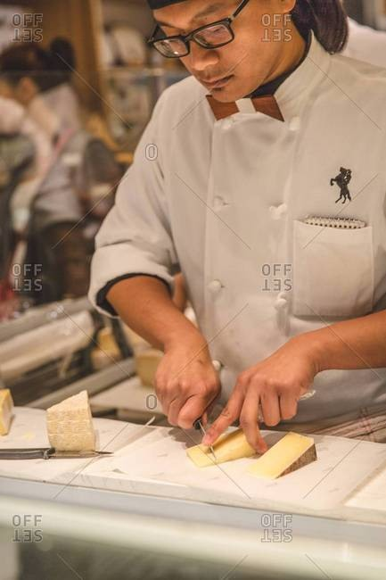 San Francisco - August 6, 2016: Chef slicing artisan cheese