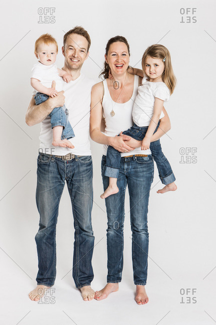 Happy family in white shirts and jeans posing together