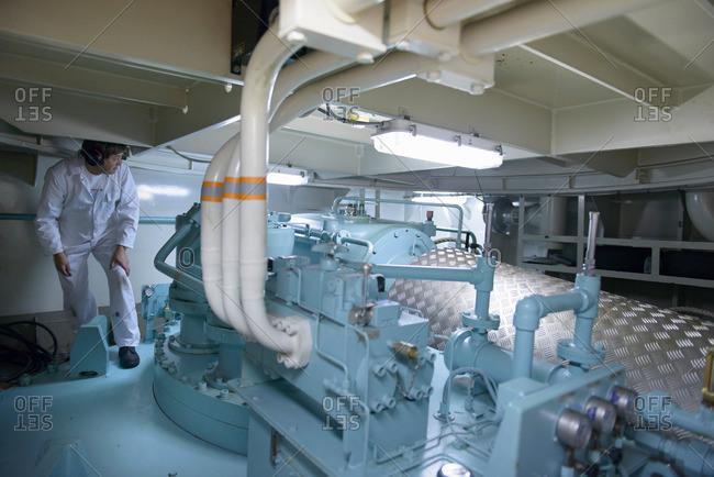 Engineer wearing ear defenders crouching under piped in ship's engine room