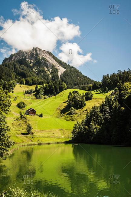 Grassy hillside by still rural lake