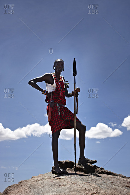 Maasai man standing on top of rock with a spear