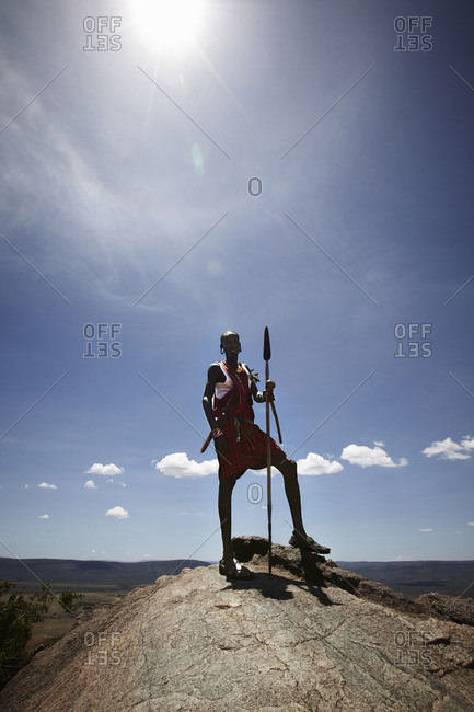 Maasai man posing on top of rock with a spear