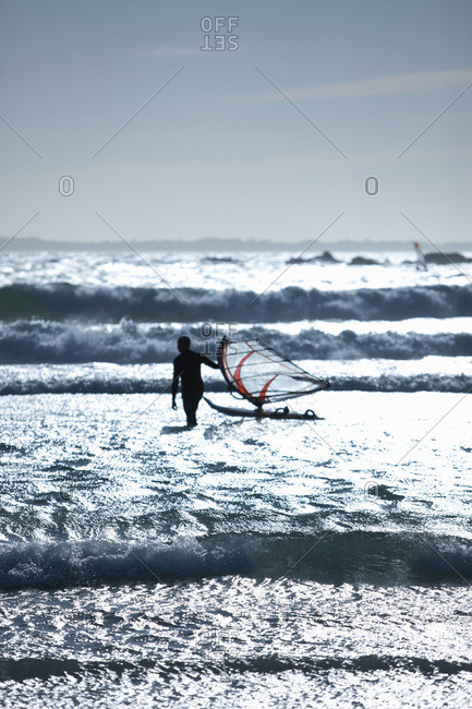 Man with wind sailing board in waves