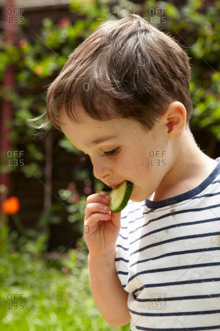 Boy eating cucumber outdoors