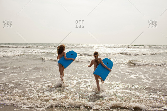 Girls carrying boogie boards in waves