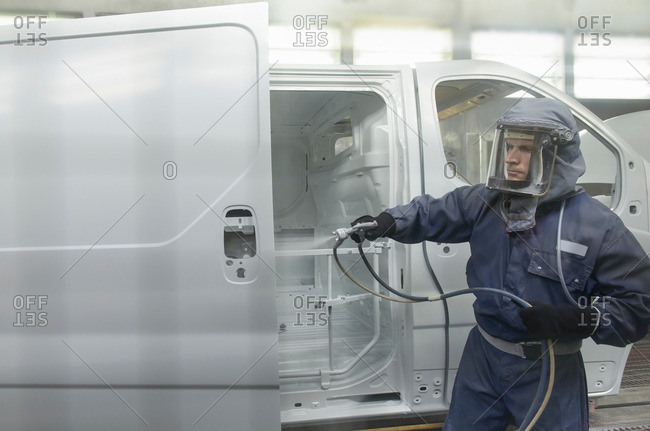 Worker wearing protective suit and mask spray painting van body