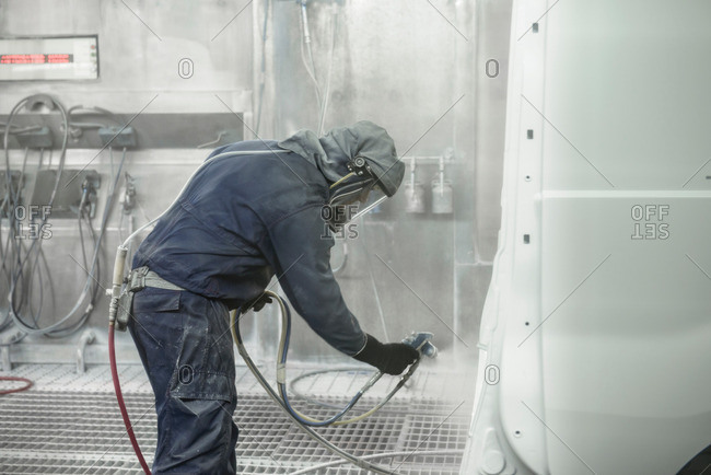 Worker wearing protective suit and mask spray painting van body in car factory